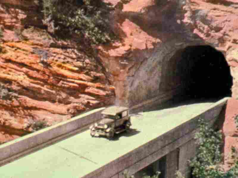 This 1930s-era hand-colored photograph shows the east side of Zion Tunnel, where a bridge was built to span a steep and narrow canyon. Credit: National Park Service