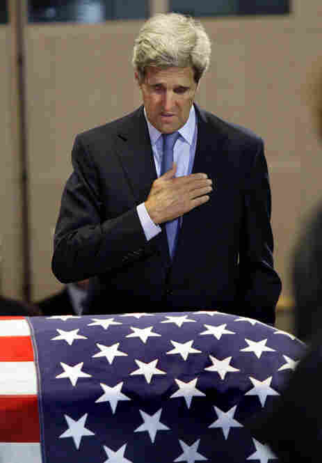 Sen. John Kerry, D-Mass., pays his respects at Kennedy's flag-draped casket inside the JFK Library in Boston Friday.