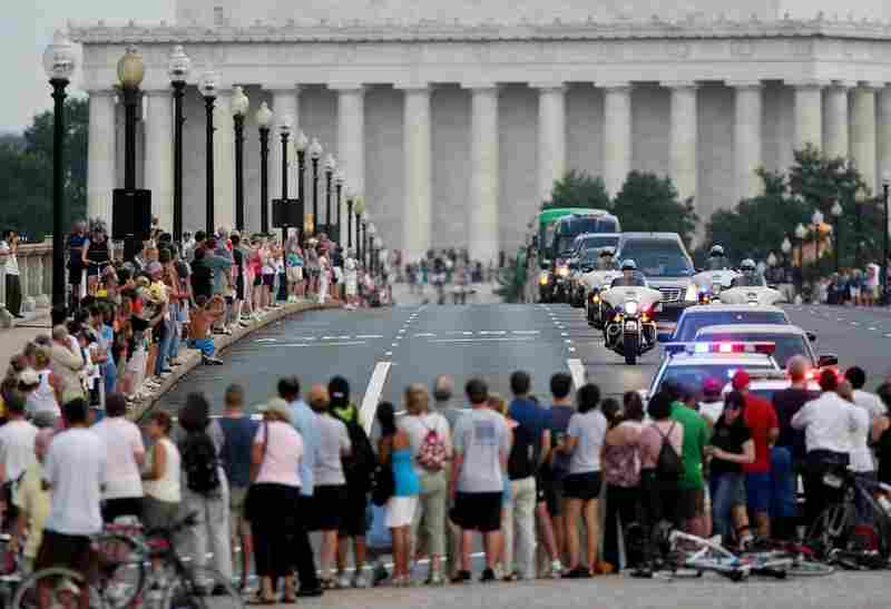 Spectators watch the motorcade for Kennedy cross Memorial Bridge on its way to Arlington National Cemetery. The Lincoln Memorial is in the background.