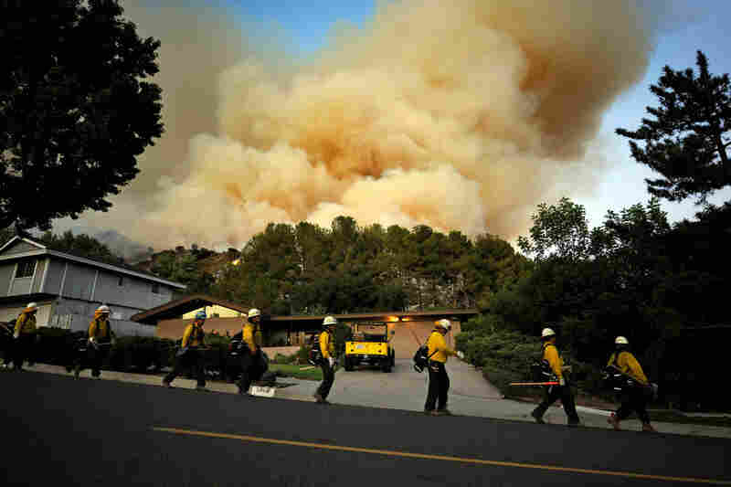 A U.S. Forest Service hand crew walks down a street Monday as a backfire lights up a hillside in La Crescenta, Calif.