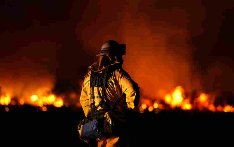 A Los Angeles County firefighter monitors hot spots Sunday as a wildfire cuts a swath through Acton, Calif.