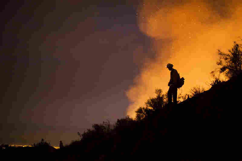 On Friday, a firefighter watched for stray embers that could ignite unburned vegetation.
