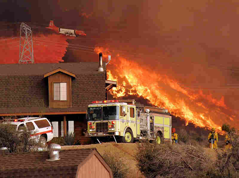 A United States Forest Service air tanker drops fire retardant in the hills above a home in Acton on Sunday.
