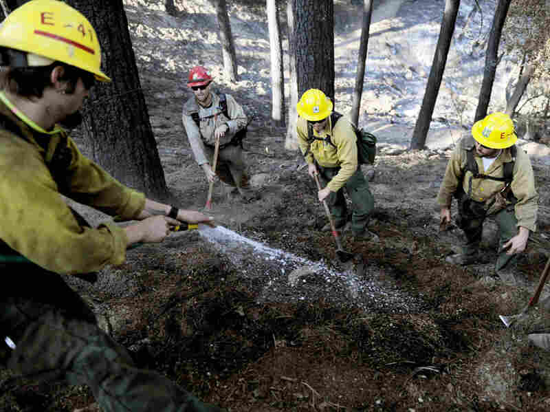 Firefighters mop up along a ridge near Mount Wilson after wildfires invaded the Angeles National Forest near Los Angeles on Monday.