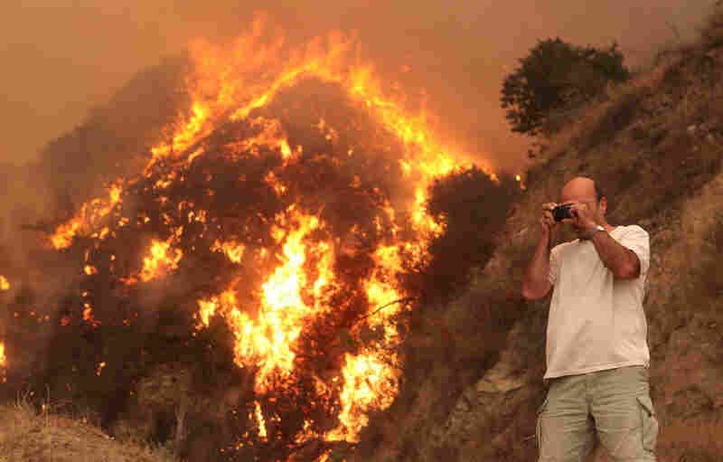 Firefighters attempted to take control of the fire with controlled backfires and brush clearing techniques. A resident of Tujunga, Calif., takes a photograph near his home  Tuesday.