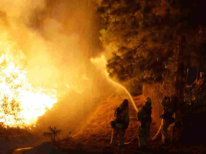 Firefighters work to hold back a fire threatening houses in the La Crescenta section of Glendale, Calif. Tuesday.
