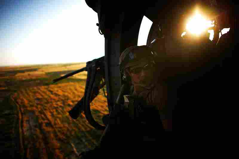 United States Air Force Senior Airman pararescue jumper Andrew Rios hangs out the door of an HH-60 Pave Hawk while in flight to pick up an Afghan policeman injured in an IED attack in Kandahar, southern Afghanistan.