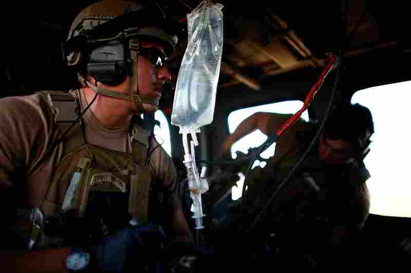 CSAR pararescue jumpers Andrew Rios (left) and Mark Bedell stabilize the policeman while in flight to the hospital.