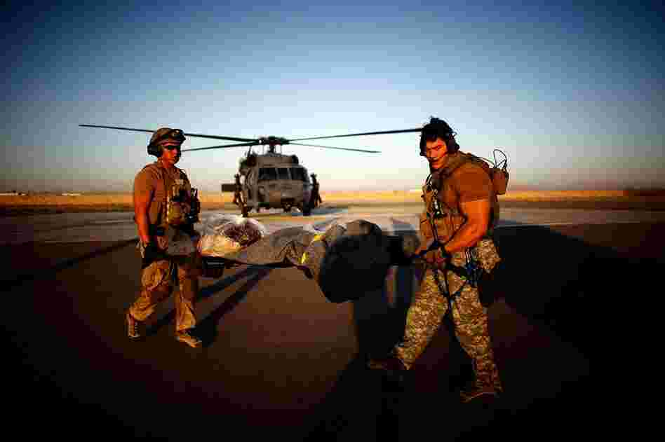 Pararescue jumpers Rios (left) and Bedell transport the policeman to the Afghan ambulance.
