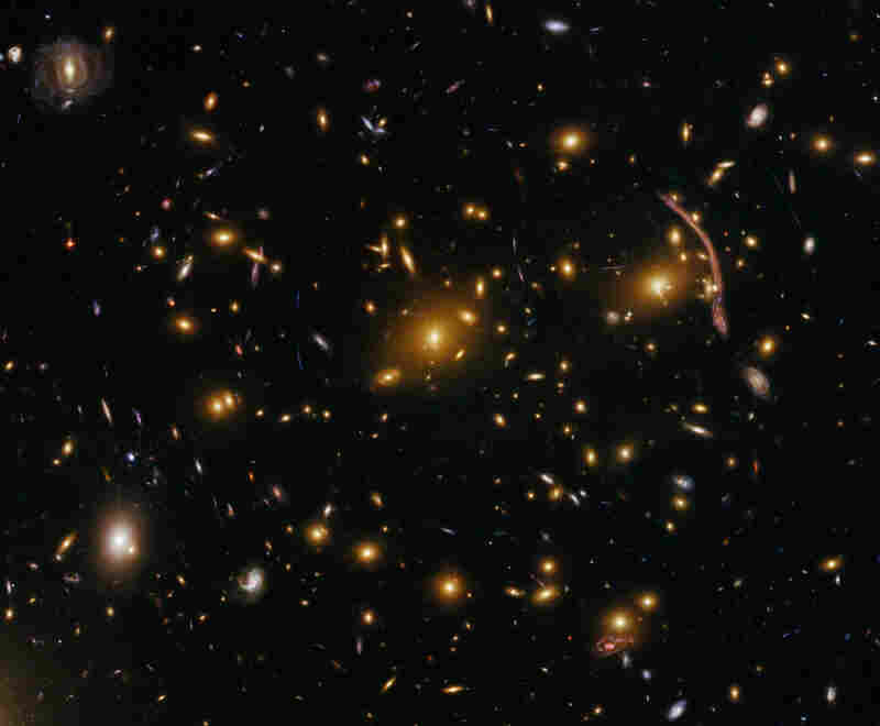 An image of the galaxy cluster Abell 370, located nearly 5 billion light years away, was taken July 16, 2009. Abell 370 is one of the first galaxy clusters in which astronomers observed the phenomenon of gravitational lensing, where the cluster's gravitational field distorts the light from galaxies behind it.