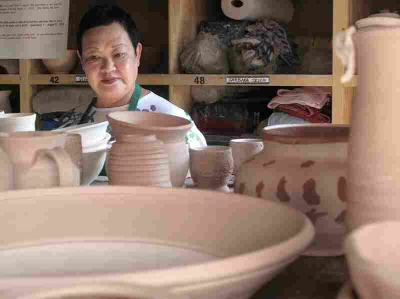 Shinko looks for her own pieces, among the dried pots waiting to be glazed.