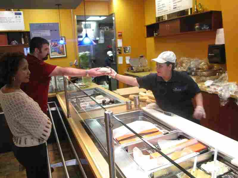 Lara hands a customer his meal.
