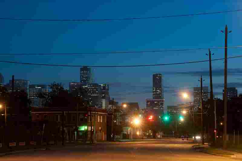 The contrast between downtown Houston and the Third Ward can be seen from a deserted street at night.