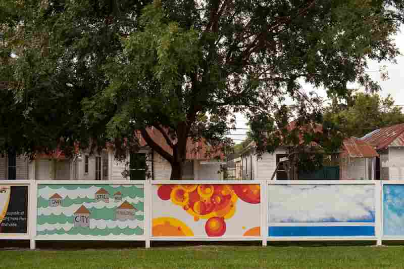 A mural proclaiming the need for rebuilding the city stands in front of a series of shotgun houses in the Third Ward.