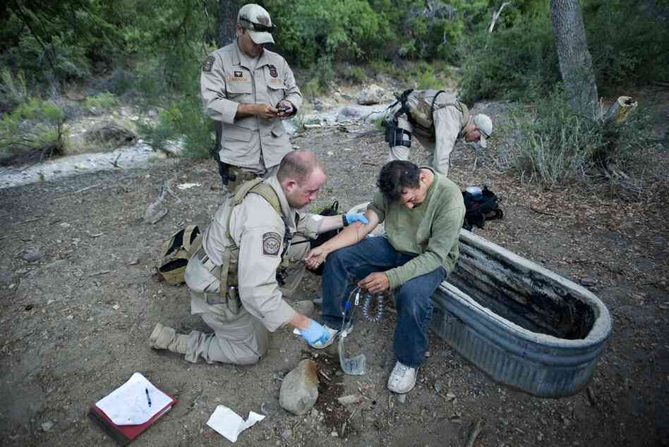 Border Patrol Search, Trauma, and Rescue teams are trained to help distressed migrants and border agents in the desert. BORSTAR agent Jared Ashby (left) gives medical aid to Victor Manuel Lopez-Galindo near Red Canyon, Ariz., on June 11. Lopez-Galindo had been attacked and robbed by drug smugglers. He finally started a fire to signal for help after hiking five days in the desert with 1 gallon o...