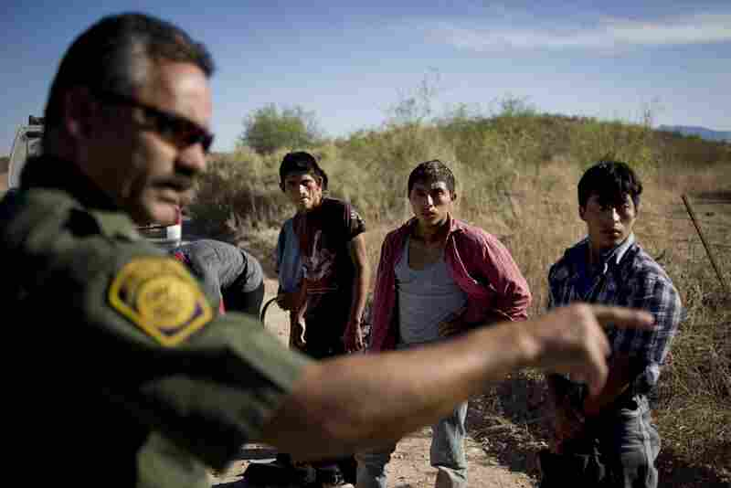 A Border Patrol agent lines up a group of immigrants caught while passing through the desert along highways 286 and 86 in Tucson, Ariz.., on June 10. When migrants are found by the Border Patrol they are returned to the border, where many will attempt the five-day hike to get into the United States several times.