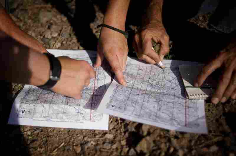 No More Deaths volunteers look at trail maps to decide where a water drop patrol will take place outside Arivaca, Ariz. Members of the group have spent years walking the trails in the Arivaca region to track migrant crossing patterns.