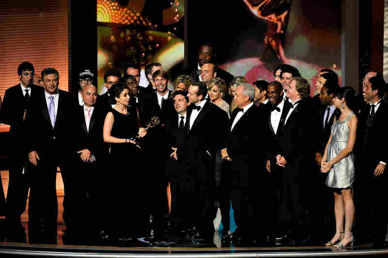 Tina Fey, star and executive producer of 30 Rock, accepts the comedy series award surrounded by the show's cast and crew.