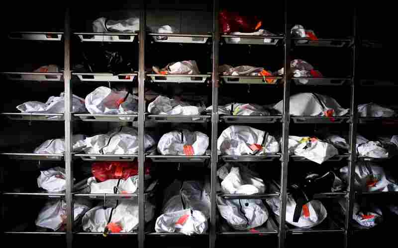 Rows of body bags containing remains of unidentified people found in the desert sit in a cooler outside the Pima County Medical Examiner's Office in Tucson on Aug. 12. The identification process can take years for each body, resulting in an overflowing caseload for the medical examiner.