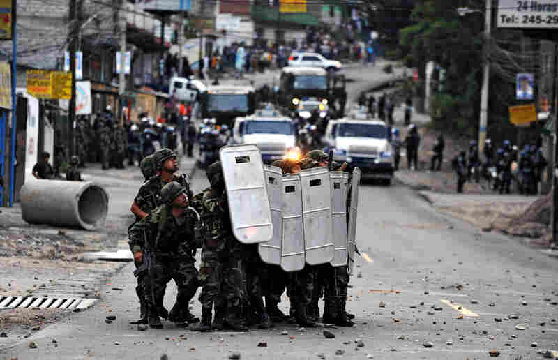 Soldiers take cover during clashes with protesters in the El Pedregal neighborhood.
