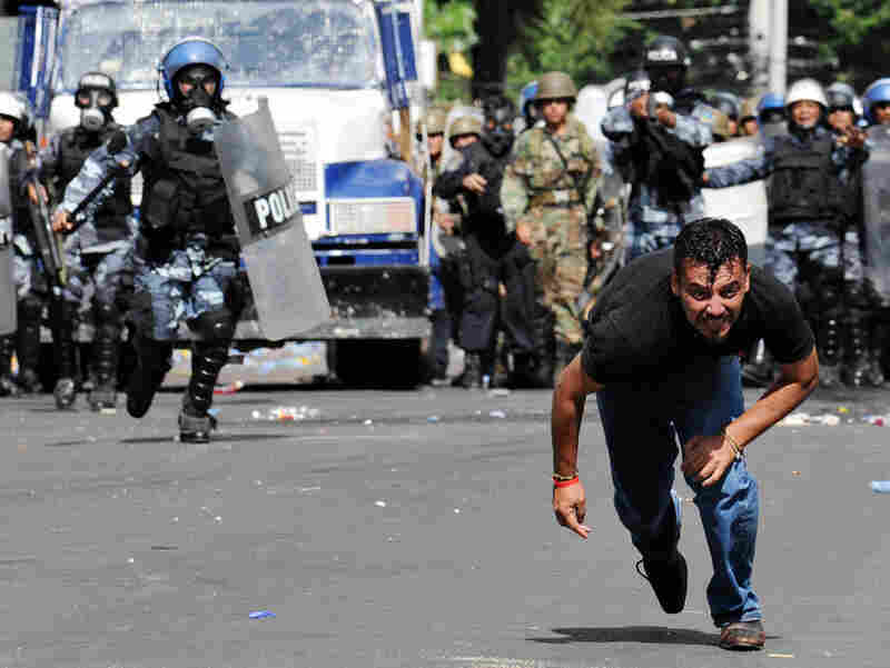 A protester runs from police during riots near the Brazilian Embassy in Tegucigalpa on Wednesday.
