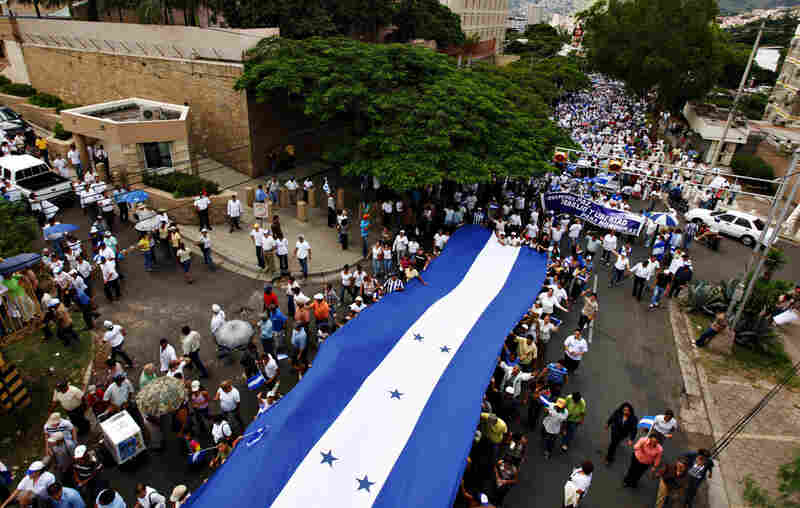Zelaya's opponents carry a Honduran flag past the U.S. Embassy in Tegucigalpa on Thursday.