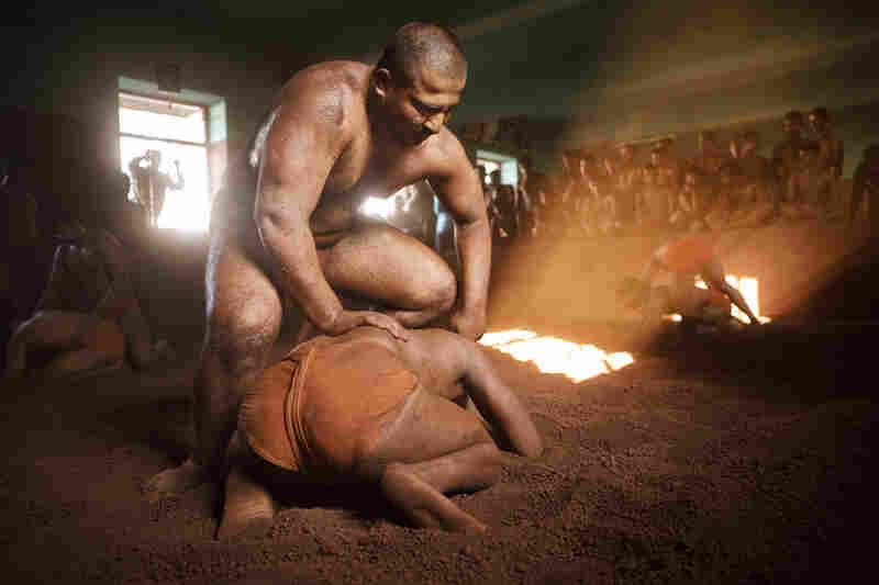 Wrestlers practice Kushti,  India's ancient form of wrestling on red soil.