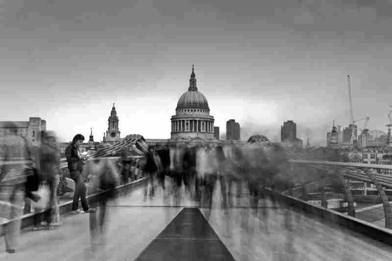 Workers rush along Millennium Bridge in London, England, while one tourist takes her time relaxing by the bridge.
