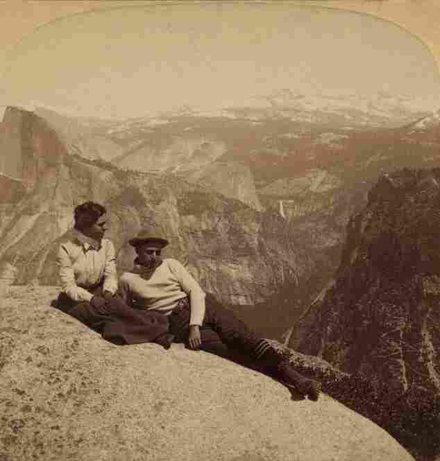 A man and woman lounge on Eagle Rock in Yosemite National Park, circa 1902.