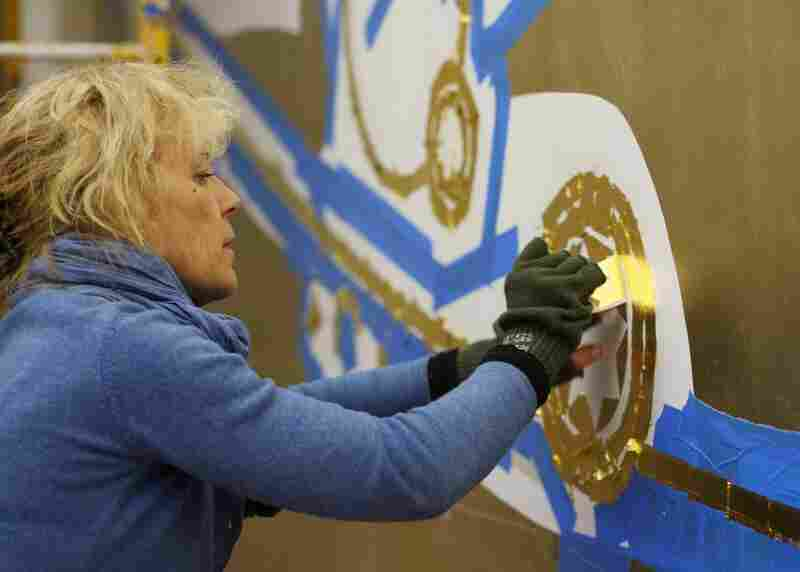 The Celestial Mural was covered up in the 1960s during a project to modernize the lobby and level the lights. Here, a restoration artist applies gold leaf to the mural.