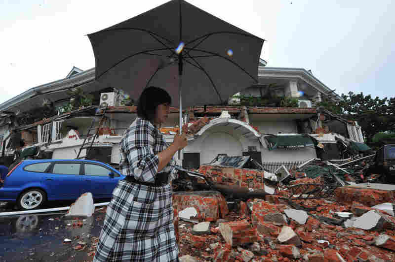 A woman walks past a collapsed hotel Thurs., Oct. 1 in Padang. More than 500 buildings were destroyed or damaged by the earthquakes.