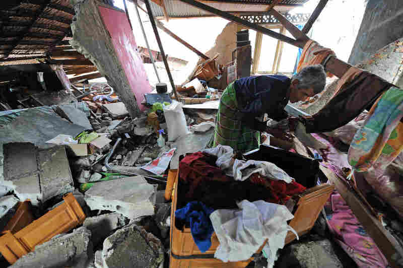 An Indonesian man salvages belongings from his destroyed home Thurs., Oct. 1 in Padang.