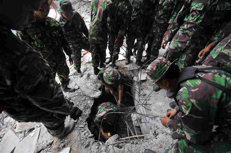 Indonesian soldiers search for survivors in a crumbled building Thurs., Oct. 1 in Padang, Sumatra. Officials said that 376 people have died and more than 400 were seriously injured.