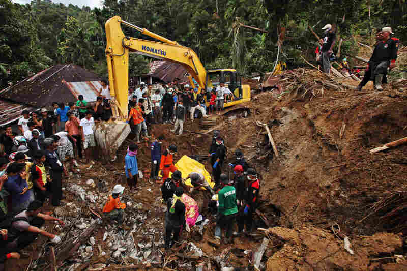 Rescue volunteers cover a body before removing it from an area severely hit by landslides in the Sumatran Island village of Jumanak, on Sun., Oct. 4.