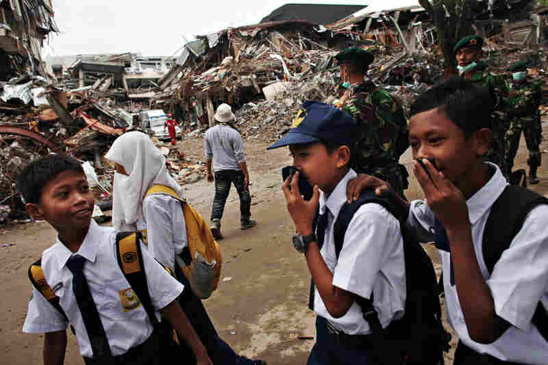 Indonesian students walk past the rubble of the Amberchang Hotel Monday on their way to school for the first time since a pair of earthquakes struck Padang, Indonesia on Sept. 30 and Oct. 1.