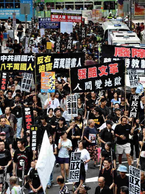 In Hong Kong, pro-democracy demonstrators hold up placards as they walk toward China's liaison office Thursday. Scuffles broke out between protesters and police, as hundreds took to the streets to urge Chinese leaders to improve human rights and release jailed dissidents.