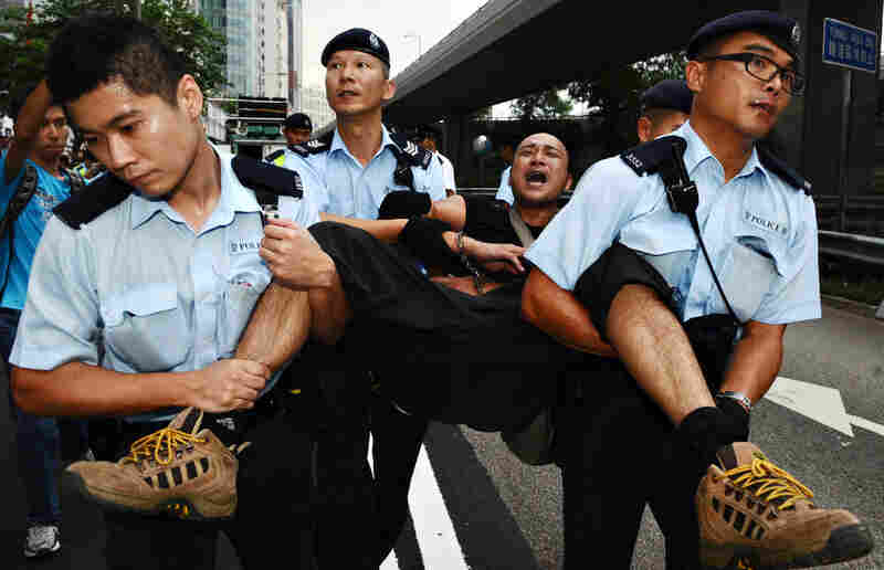 Police in Hong Kong carry away a pro-democracy demonstrator after a scuffle ensued when protesters attempted to make their way to China's liaison office Thursday.