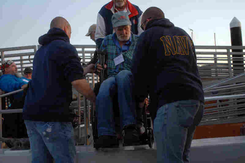 Volunteers help Navy veteran Stephen Snell board the fishing boat Chubasco. This boat is one of four used for the derby.