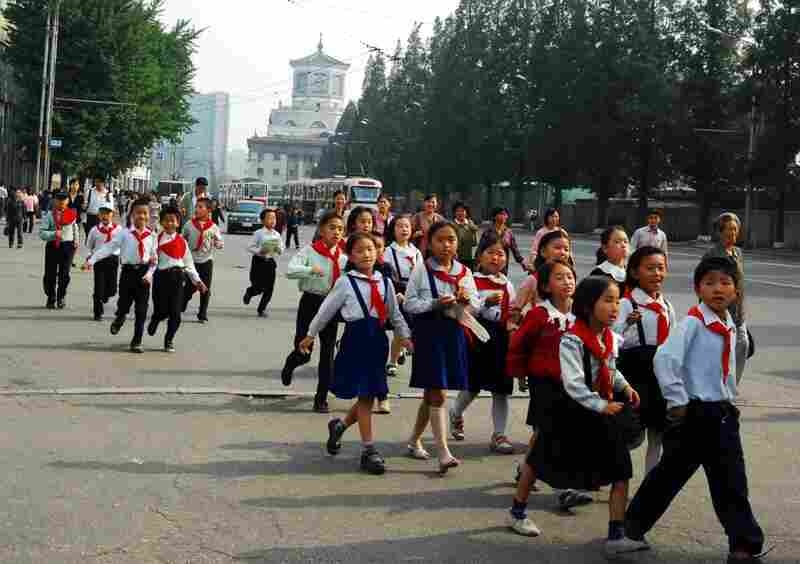 A group of schoolchildren walks along the street outside Yanggwang Station in Pyongyang.