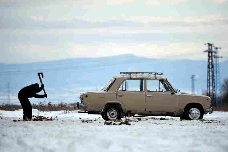 A boy chops wooden pallets next to a Russian-made Lada in the suburbs of Sofia, Bulgaria, in January.