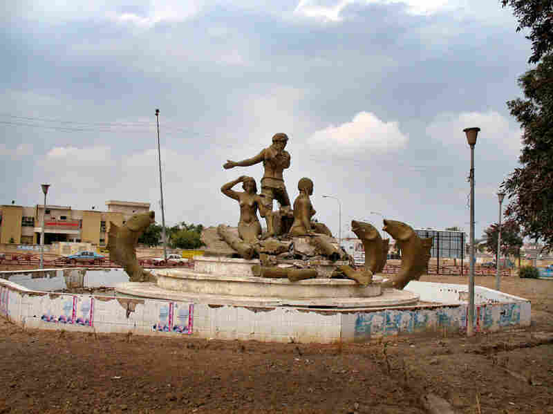 """Tayaran Square: """"The religious men who are running my city, on behalf of God, have destroyed the statues of the city because they say they are haram [forbidden]. They've targeted female sculptures, but left the fish and the men alone.  Women's bodies are 'shameful', it seems, even if they are made of brass."""""""
