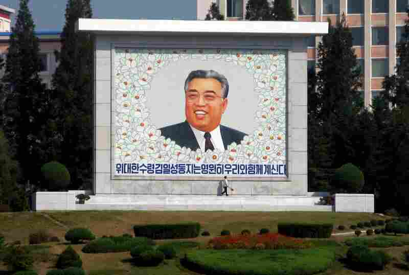 "There are an estimated 140,000 monuments to Kim Il Sung in the country. Here, a street sweeper cleans a giant picture of the man North Koreans call the ""Great Leader."""