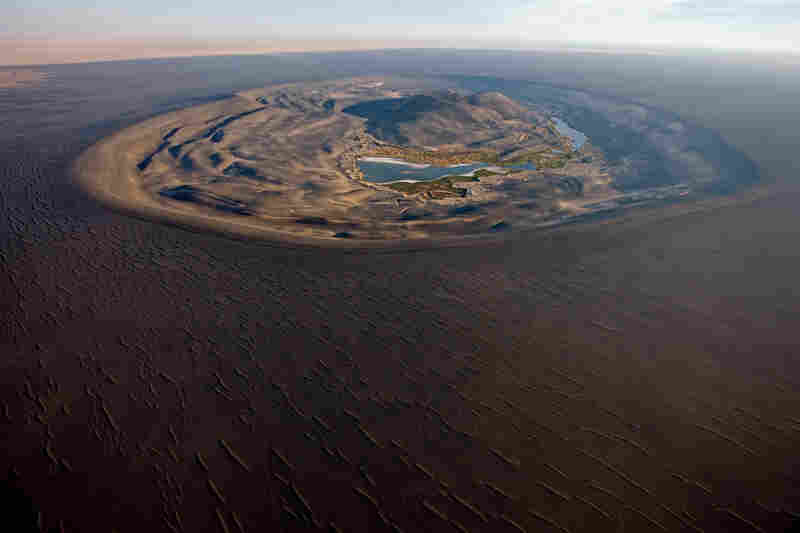 Waw an Namus is a volcanic field in the southern area of Libya, in the heart of the Sahara. Water from rains that fell millennia ago pools in the crater. Winds carried black ash from the last eruption 12 miles out across the desert.