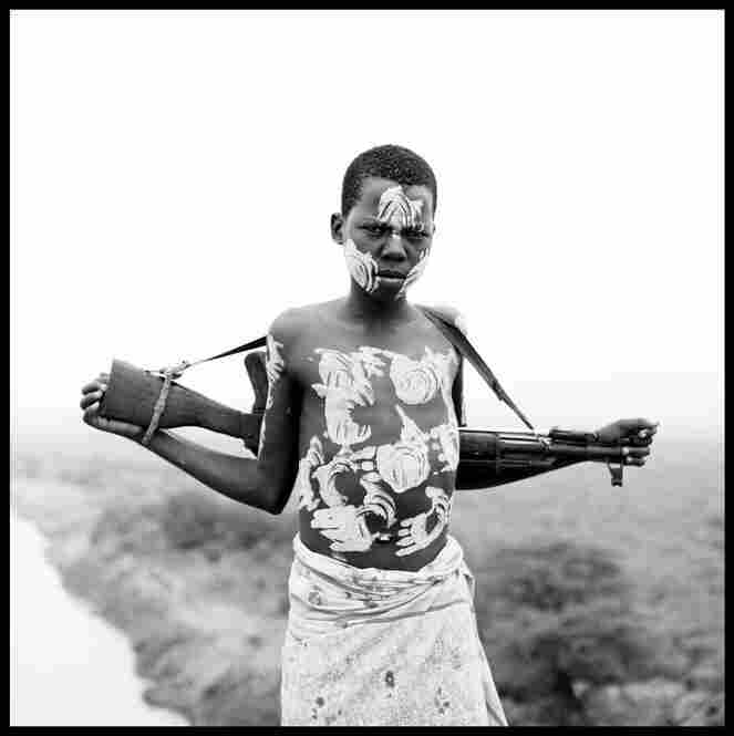 """A young boy holds a rifle on his back after decorating his body with white paint overlooking the Omo River in remote Ethiopia."""