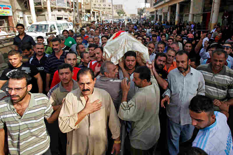 Mourners carry the coffin of a victim killed in Sunday's suicide bombing in Baghdad during a funeral procession Monday. Iraqi security forces blocked streets near the capital as authorities investigated the pair of bombings that killed more than 150.