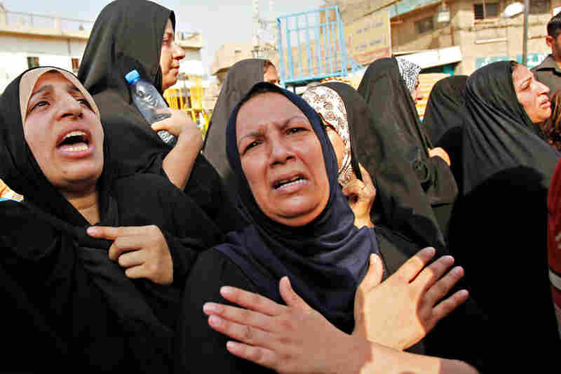 Funeral services were held throughout the city on Monday. The attacks targeted Baghdad's provincial council and the Justice Ministry, and were the deadliest in the capital since 2007.