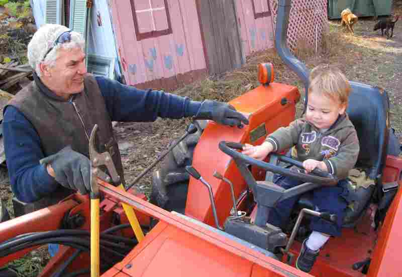 """Sam lets Lincoln """"drive"""" his tractor."""