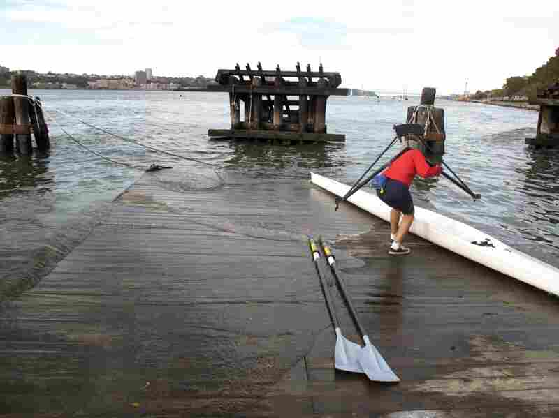 As the pier begins to move and water washes over the edge, Cumella quickly picks up his oars and scull before they're swept into the river.
