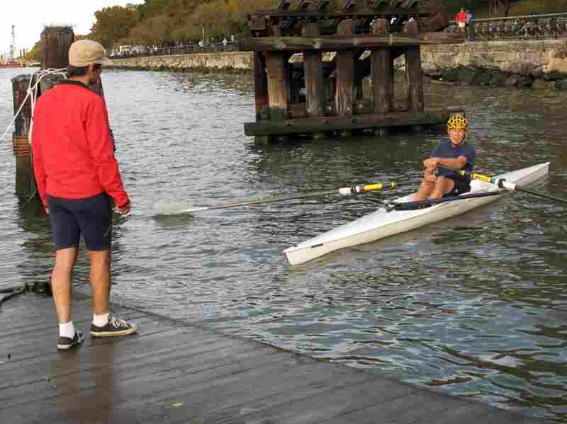 Sculls go faster than kayaks because they're propelled by the user's legs, not just the oars, and Thomas quickly heads upriver, until he's little more than a dot on the water.