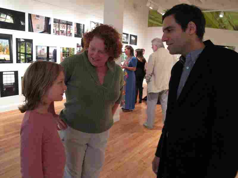 Artist Michael Lease (right) greets visitors.